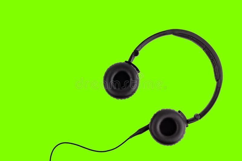 Μαύρα ακουστικά που απομονώνονται στο πράσινο υπόβαθρο στοκ εικόνες