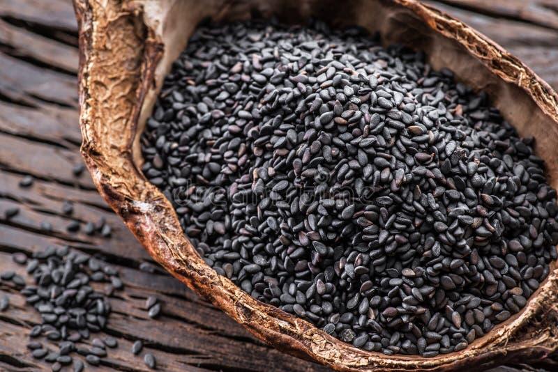 Μαύροι σπόροι σουσαμιού στο οργανικό κύπελλο στον παλαιό ξύλινο πίνακα Τοπ όψη στοκ εικόνες με δικαίωμα ελεύθερης χρήσης
