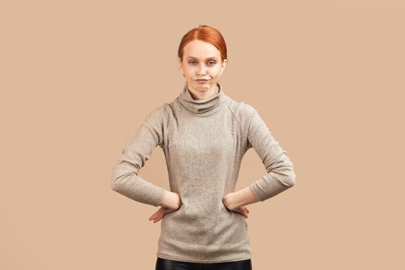 Μεμβρανοειδής γυναίκα με τη λυπημένη και απογοητευμένη έκφραση, που κρατά τα χέρια και στις δύο πλευρές στοκ εικόνες