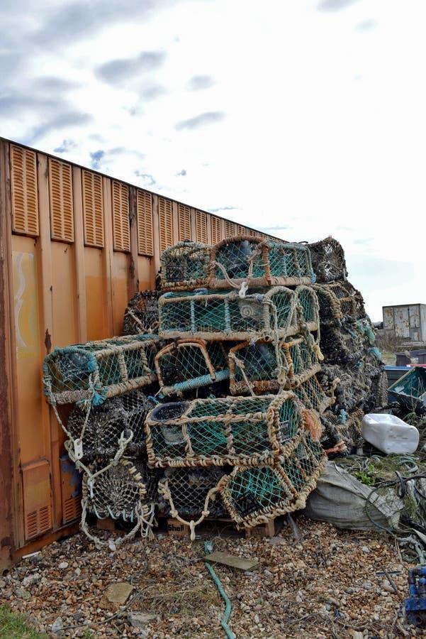 Μερικά crabbing δοχεία που τυλίγονται στο δίχτυ του ψαρέματος που συσσωρεύεται ενάντια σε ένα μεγάλο εμπορευματοκιβώτιο στοκ εικόνα με δικαίωμα ελεύθερης χρήσης