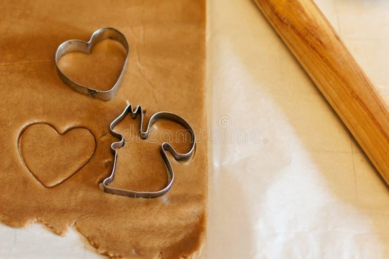 Μερικές μορφές κοπτών μπισκότων στην ακατέργαστη ζύμη μπισκότων, μια με τη μορφή καρδιών, ένα άλλο ένα - σκίουρος Ξύλινος κύλινδρ στοκ εικόνα