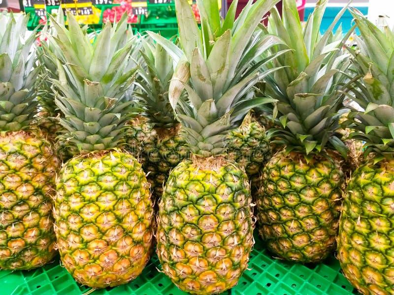 μερικοί φρέσκοι ανανάδες σε ένα πλαστικό πράσινο ράφι σε μια αγορά έτοιμη να πωληθεί στους πελάτες πράσινη οριζόντια βλάστηση ουρ στοκ εικόνες