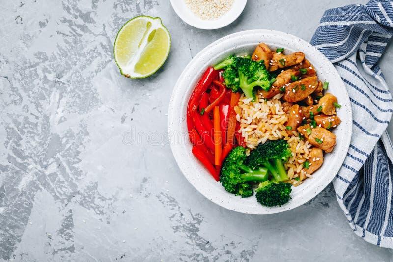 Μεσημεριανό γεύμα κύπελλων του Βούδα κοτόπουλου Teriyaki με το ρύζι, το μπρόκολο και το κόκκινο πιπέρι κουδουνιών στοκ εικόνες