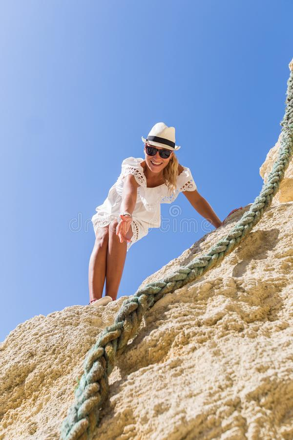 Με ακολουθήστε! Το κορίτσι στέκεται στο βράχο και φθάνει έξω στο χέρι της στοκ φωτογραφίες