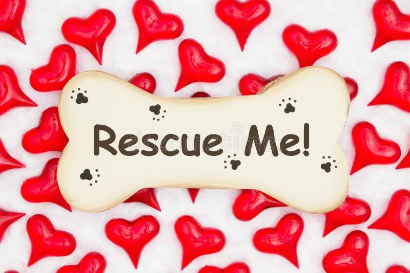 Με διασώστε μήνυμα σε ένα ξύλινο κόκκαλο σκυλιών με την τυπωμένη ύλη ποδιών με τις κόκκινες καρδιές στο άσπρο ύφασμα στοκ εικόνες