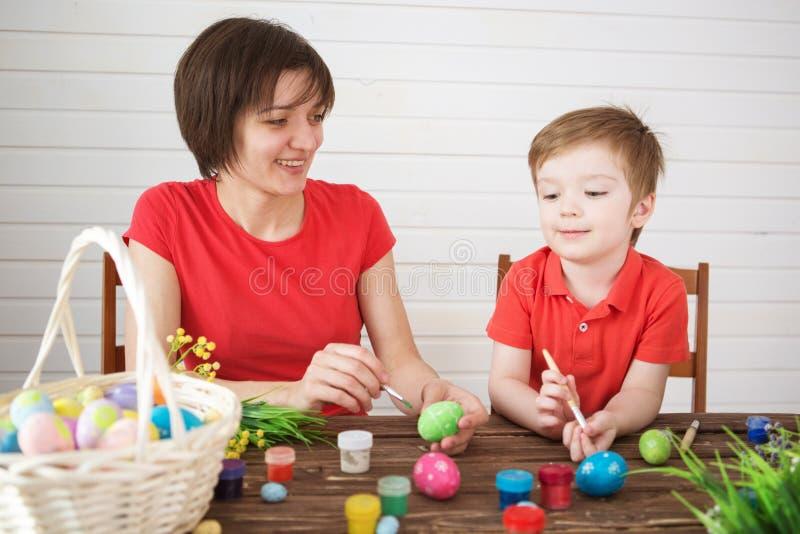 Μητέρα και γιος που χρωματίζουν τα αυγά Πάσχας Ευτυχής οικογένεια Mom και αυγά Πάσχας χρωμάτων γιων παιδιών με τα χρώματα Προετοι στοκ εικόνα