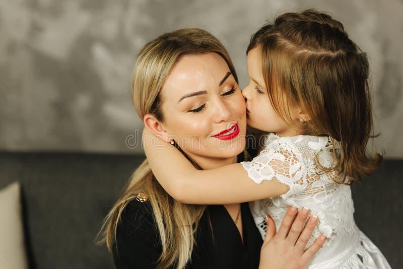 Μητέρα και χαμόγελο αγκαλιάσματος μικρών κοριτσιών Ευτυχές νέο mom με την κόρη της στο σπίτι στοκ φωτογραφία