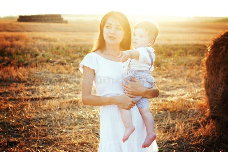 Μητέρα που αγκαλιάζει το παιδί της κατά τη διάρκεια του περιπάτου στο πάρκο πέρα από το ηλιοβασίλεμα στοκ φωτογραφία με δικαίωμα ελεύθερης χρήσης