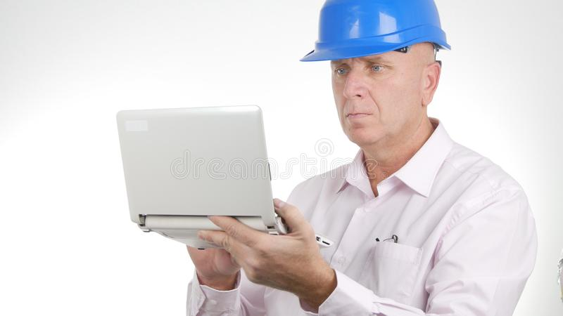 Μηχανικός που εργάζεται χρησιμοποιώντας ένα lap-top που έχει πρόσβαση στις σε απευθείας σύνδεση τεχνικές πληροφορίες στοκ φωτογραφία με δικαίωμα ελεύθερης χρήσης