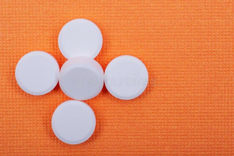 Μη-steroidal αντιφλεγμονώδη φάρμακα Άσπρες ταμπλέτες Acetaminophen στο πορτοκάλι στοκ εικόνα