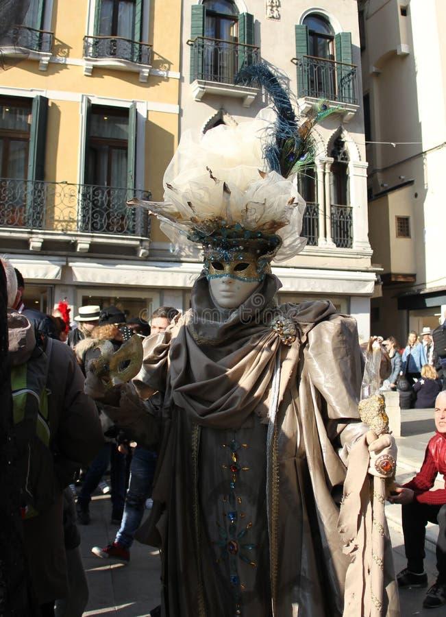 Μια άσπρη μάσκα με τις χρυσές λεπτομέρειες δίπλα στα μάτια Βενετία καρναβάλι 2019 στοκ εικόνες