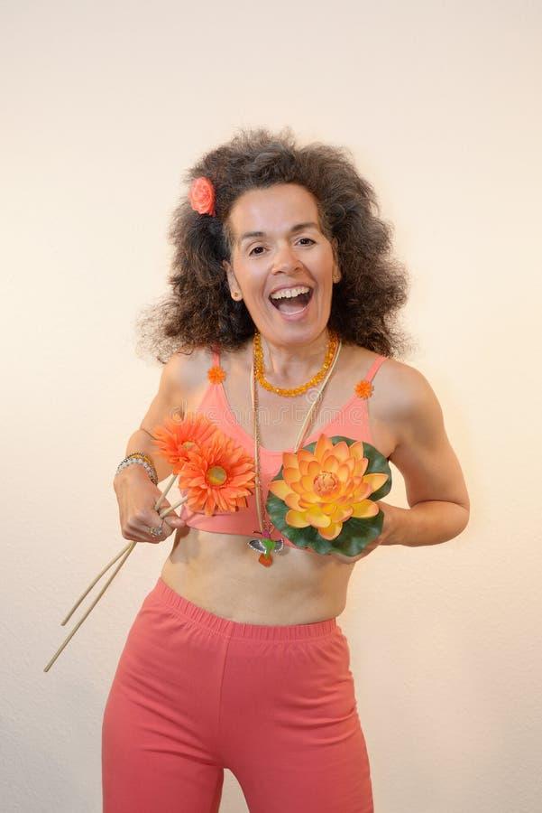 Μια γυναίκα άνω των 50 που θέτουν με τα συναισθήματα ανοίξεων λουλουδιών στοκ εικόνες