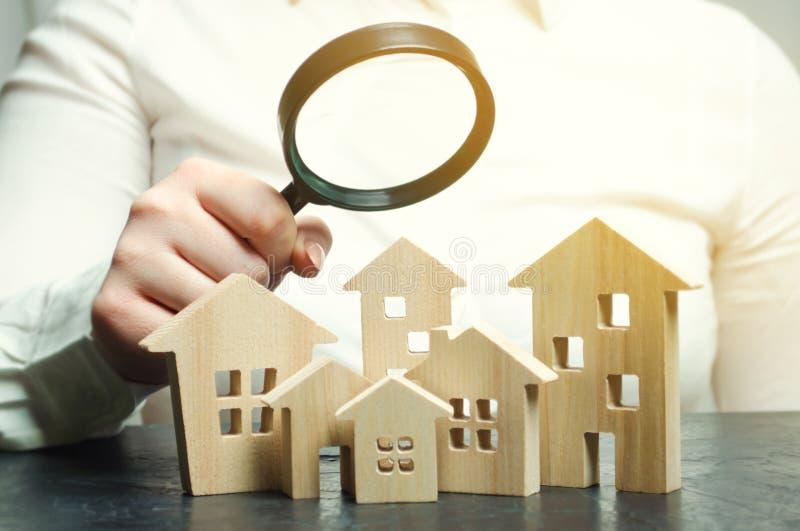 Μια γυναίκα κρατά μια ενίσχυση - γυαλί πέρα από ξύλινα σπίτια Εκτιμητής ακίνητων περιουσιών Αξιολόγηση/αξιολόγηση ιδιοκτησίας Βρε στοκ φωτογραφία