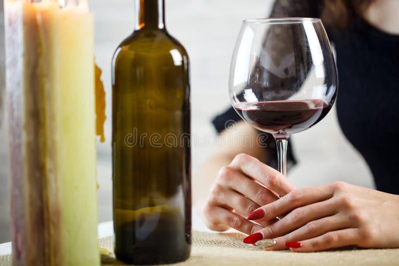 Μια γυναίκα κρατά στο χέρι της ένα ποτήρι του κρασιού σε ένα ραντεβού στα τυφλά Wineglass δύο στον πίνακα κλείστε επάνω στοκ εικόνες