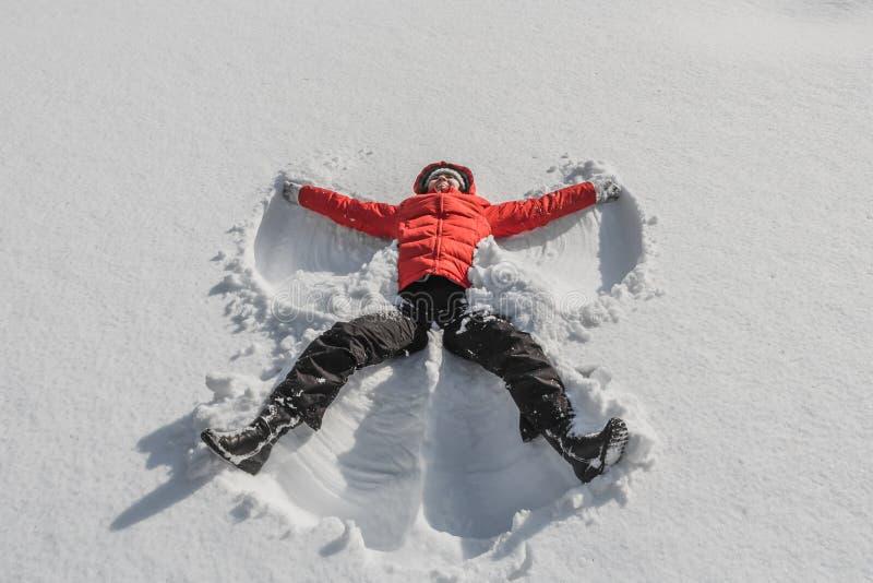 Μια γυναίκα σε ένα κόκκινο σακάκι και το Μαύρο ασθμαίνει σε ένα άσπρο χιόνι σε ένα χειμερινό πάρκο Μια γυναίκα βρίσκεται στο χιόν στοκ εικόνα με δικαίωμα ελεύθερης χρήσης