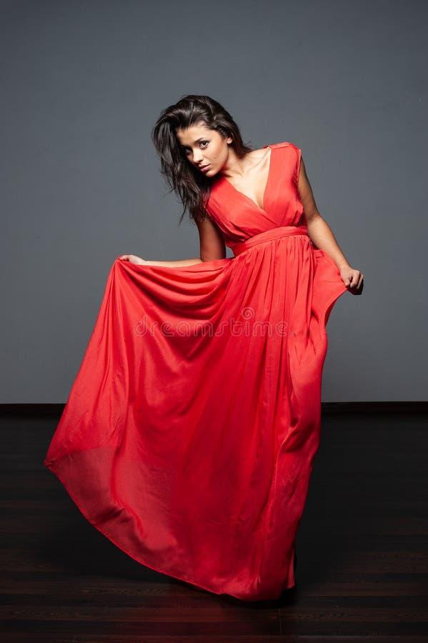 Μια γυναίκα σε ένα κόκκινο φόρεμα στοκ εικόνες
