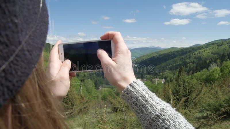 Μια γυναίκα παίρνει τις εικόνες στα πλαίσια των μεγάλων βουνών και του πράσινου ποταμού βουνών Στο τηλέφωνο selfie ή στοκ εικόνες
