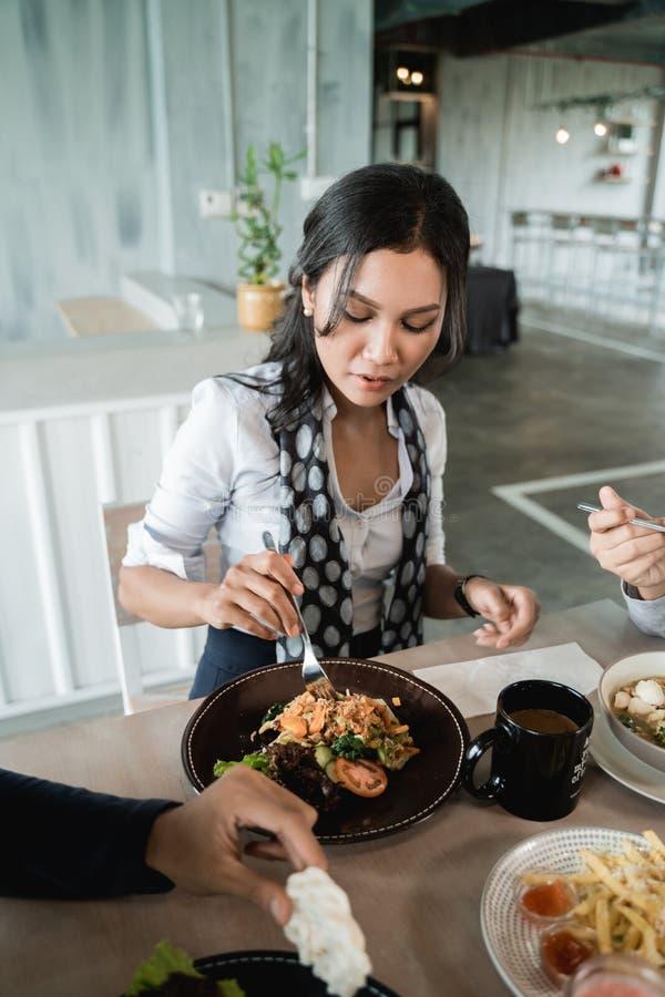 Μια επιχειρηματίας απολαμβάνει το γεύμα της όταν μεσημεριανό γεύμα από κοινού στοκ εικόνα