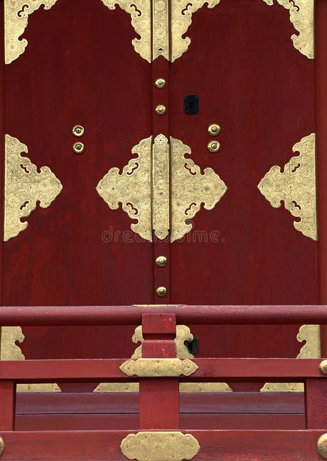 Μια ιαπωνική κόκκινη πόρτα με τις χρυσές λεπτομέρειες και κιγκλιδώματα στο μπροστινό υπόβαθρο στοκ εικόνες