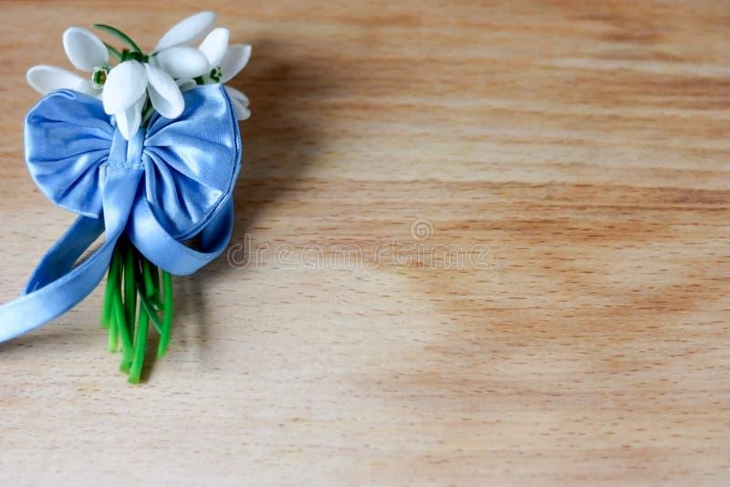 Μια μικρή ανθοδέσμη των όμορφων άσπρων snowdrops έδεσε με μια μπλε κορδέλλα με ένα τόξο μεταξιού σε ένα ξύλινο υπόβαθρο στοκ εικόνες