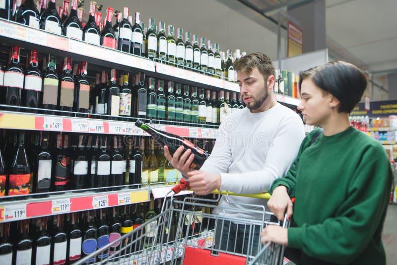 Μια νεολαία συνδέει την εξέταση ένα μπουκάλι του κρασιού σε μια υπεραγορά Νέο ζεύγος στο τμήμα οινοπνεύματος του καταστήματος στοκ εικόνες με δικαίωμα ελεύθερης χρήσης