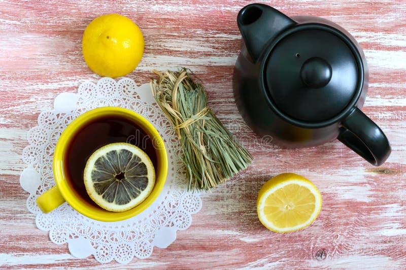 Μια δέσμη ξηρό lemongrass, του φρέσκου λεμονιού, teapot και του φλυτζανιού του τσαγιού Συστατικά τσαγιού Ο πολιτισμός της κατανάλ στοκ εικόνα με δικαίωμα ελεύθερης χρήσης
