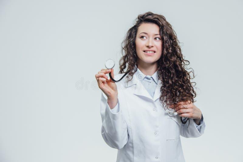 Μια σοβαρή νέα θηλυκή καυκάσια γυναίκα σε μια εργαστηριακή τήβεννο, που εξετάζει σας και που κρατά το phonendoscope από το χέρι στοκ εικόνες
