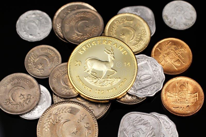 Μια στενή επάνω εικόνα των πακιστανικών νομισμάτων με ένα χρυσό νοτιοαφρικανικό krugerrand στοκ εικόνα με δικαίωμα ελεύθερης χρήσης