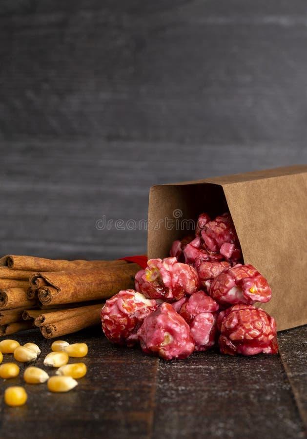 Μια τσάντα σκούρο κόκκινο Popcorn κανέλας σε έναν ξύλινο πίνακα κουζινών στοκ εικόνες με δικαίωμα ελεύθερης χρήσης