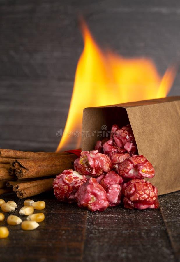 Μια τσάντα σκούρο κόκκινο Popcorn κανέλας σε έναν ξύλινο πίνακα κουζινών στοκ φωτογραφίες