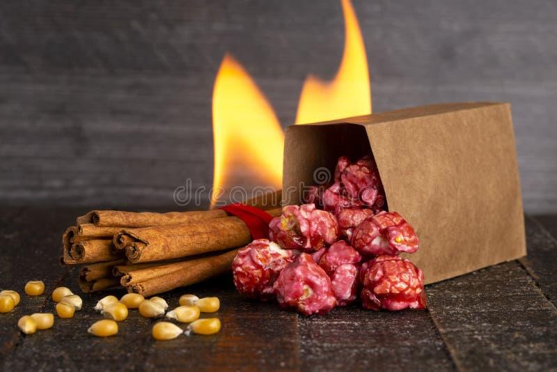 Μια τσάντα σκούρο κόκκινο Popcorn κανέλας σε έναν ξύλινο πίνακα κουζινών στοκ φωτογραφία με δικαίωμα ελεύθερης χρήσης