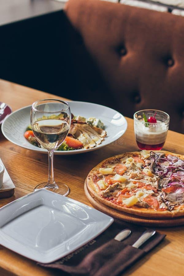 Μια φρέσκια νόστιμη πίτσα εξυπηρέτησε με το ποτήρι του άσπρου κρασιού στον ξύλινο πίνακα στο εστιατόριο στοκ εικόνες