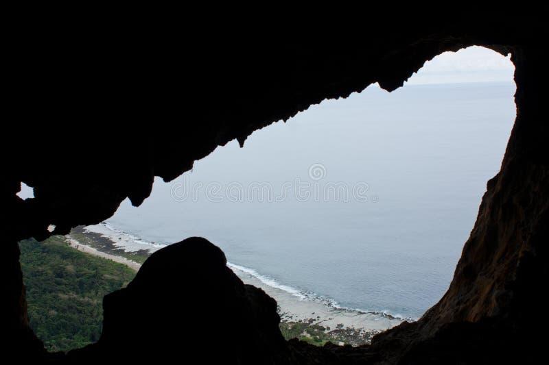 Μια παραλία και ο ουρανός που βλέπουν μέσω μιας τρύπας στο βράχο Eua στα Τόνγκα στοκ εικόνες με δικαίωμα ελεύθερης χρήσης