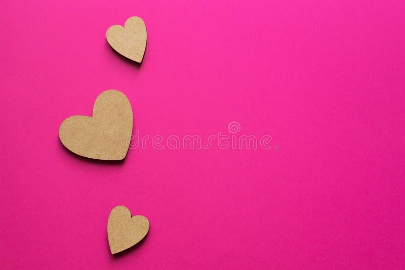Μικρές ξύλινες καρδιές στο ρόδινο υπόβαθρο Ρομαντική σύνθεση με το διάστημα αντιγράφων για το χαιρετισμό στοκ εικόνες