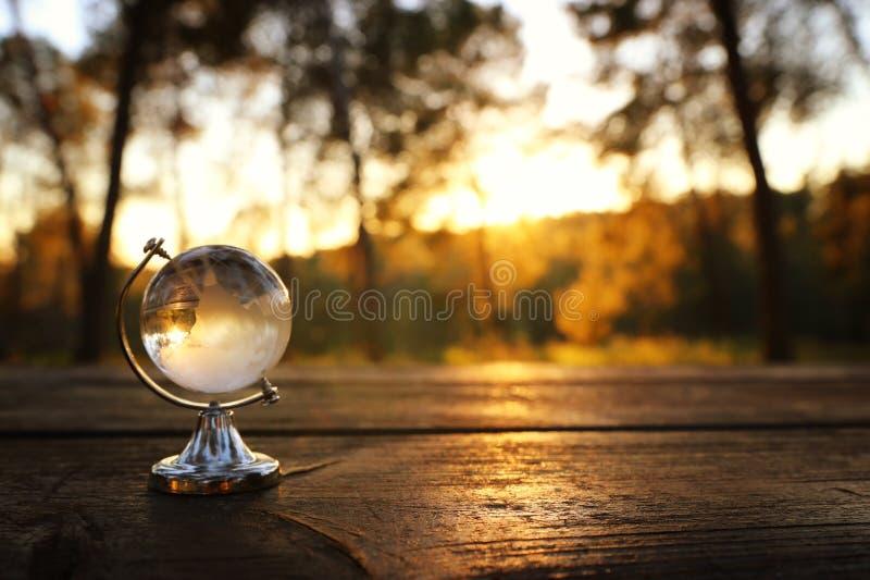 μικρή σφαίρα κρυστάλλου μπροστά από το ηλιοβασίλεμα ταξίδι και σφαιρική έννοια ζητημάτων στοκ εικόνες