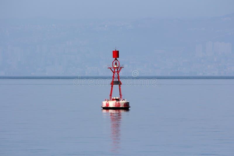 Μικρός κόκκινος πλοήγησης σημαντήρας με το φως στην κορυφή και τα ηλιακά πλαίσια για τη χρέωση που περιβάλλονται με την ήρεμη μπλ στοκ φωτογραφίες με δικαίωμα ελεύθερης χρήσης