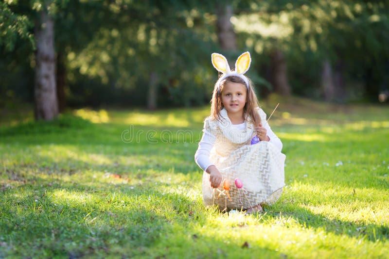 Μικρός λίγο καυκάσιο κορίτσι με τα αυτιά λαγουδάκι Πάσχας, παιχνίδι του s με τα λαϊκά ραβδιά αυγών Πάσχας, που φαίνονται απλά στη στοκ φωτογραφία