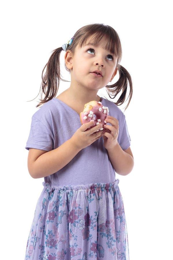 Μικρό κορίτσι σε ένα πορφυρό φόρεμα με τα donuts στοκ εικόνα με δικαίωμα ελεύθερης χρήσης