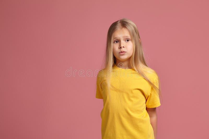 Μικρό κορίτσι σε μια κίτρινη μπλούζα φαίνεται μπερδεμένος στοκ εικόνες