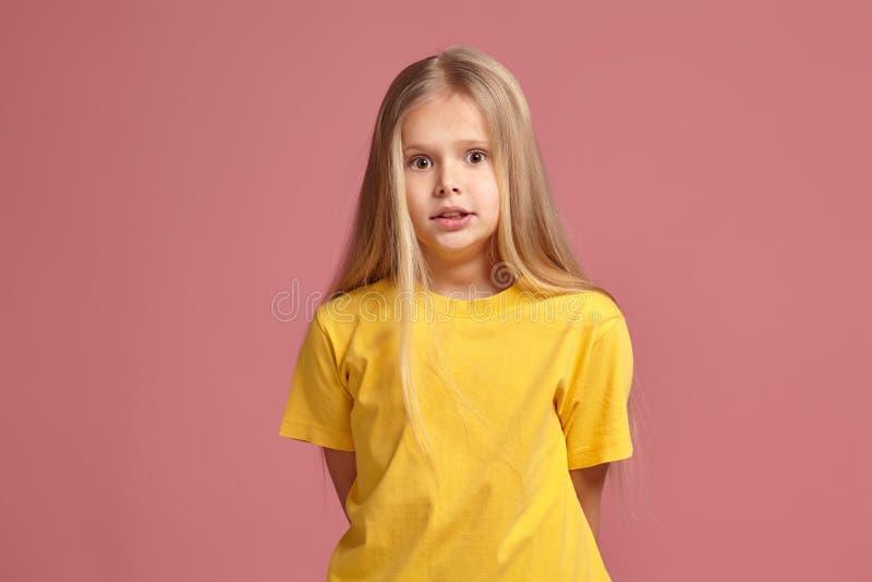 Μικρό κορίτσι σε μια κίτρινη μπλούζα φαίνεται μπερδεμένος στοκ εικόνα