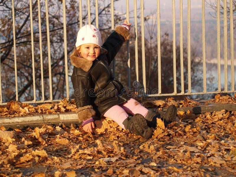 Μικρό κορίτσι που σκύβεται στα φύλλα φθινοπώρου που κρατούν επάνω σε έναν φράκτη στοκ εικόνα