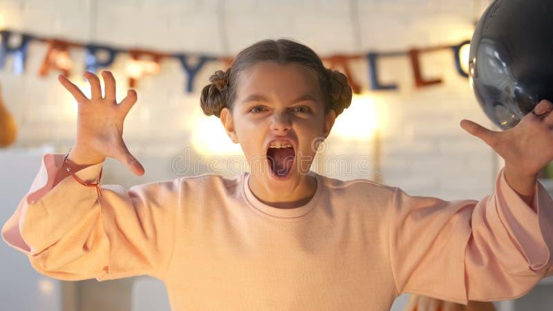 Μικρό κορίτσι που φοβίζει στη κάμερα, παραμονή εορτασμού αποκριές, που στο σπίτι στοκ φωτογραφίες