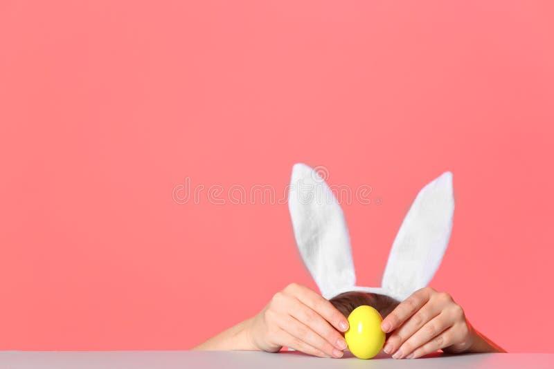Μικρό κορίτσι που φορά headband αυτιών λαγουδάκι και που παίζει με το αυγό Πάσχας στον πίνακα στο κλίμα χρώματος στοκ εικόνα