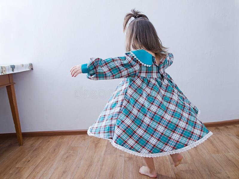 Μικρό κορίτσι που χορεύει στο σπίτι εσωτερικό παιδί στην πράσινη περιστροφή φορεμάτων στοκ φωτογραφίες
