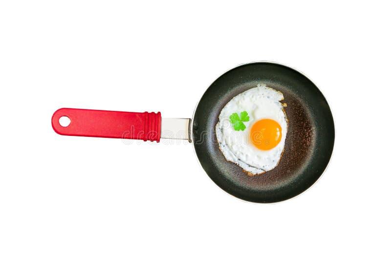 Μικρό μαύρο τηγανίζοντας τηγάνι με την κόκκινη πλαστική λαβή με το τηγανισμένο αυγό κοτόπουλου, τηγανισμένα αυγά που απομονώνοντα στοκ εικόνα