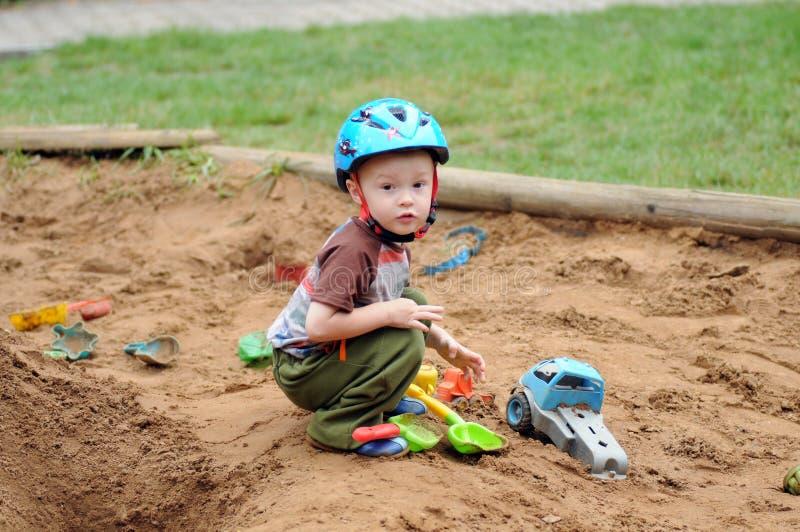 Μικρό παιδί στο Sandbox με τα παιχνίδια στοκ εικόνες