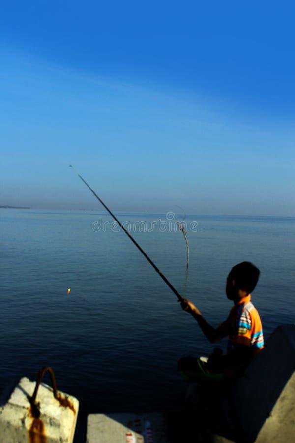 Μικρό παιδί που αλιεύει στην παραλία στοκ εικόνες