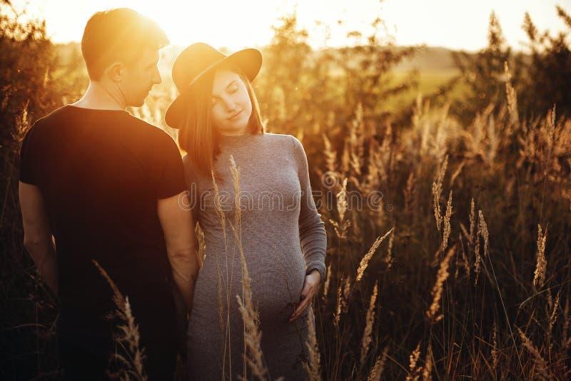 Μοντέρνα έγκυα χέρια εκμετάλλευσης ζευγών στην κοιλιά και αγκάλιασμα στο ηλιόλουστο φως στο πάρκο φθινοπώρου Ευτυχείς νέοι γονείς στοκ εικόνες