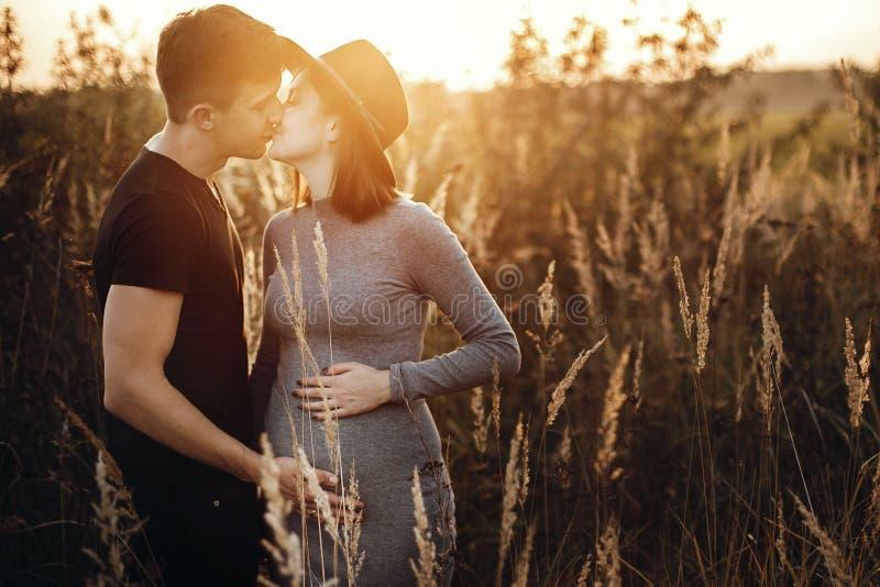 Μοντέρνα έγκυα χέρια εκμετάλλευσης ζευγών στην κοιλιά και φίλημα στο ηλιόλουστο φως στο πάρκο φθινοπώρου Ευτυχείς νέοι γονείς, mo στοκ εικόνες