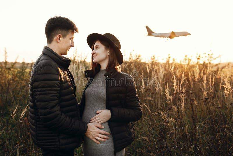 Μοντέρνα έγκυα χέρια εκμετάλλευσης ζευγών στην κοιλιά στο ηλιόλουστο φως στο πάρκο φθινοπώρου Ευτυχείς νέοι γονείς, mom και μπαμπ στοκ φωτογραφία
